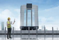 Trabalhador da construção asiático feliz com o modelo que está no terra Imagem de Stock Royalty Free