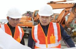 Trabalhador da construção com equipamento pesado no fundo Fotografia de Stock