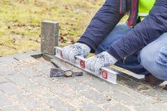 Trabalhador da construção com nível de espírito perto do pavimento inacabado fotografia de stock