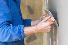 Trabalhador da construção com pá de pedreiro longa que emplastra uma parede Fotografia de Stock Royalty Free