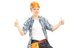 Trabalhador da construção de sorriso com o capacete que dá os polegares acima Fotografia de Stock