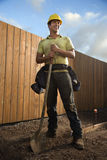 Trabalhador da construção de sorriso com uma pá Fotografia de Stock Royalty Free
