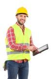 Trabalhador da construção de sorriso que usa uma tabuleta digital à prova de choque fotografia de stock
