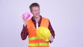 Trabalhador da construção do homem novo que pensa ao agitar o mealheiro video estoque