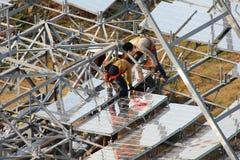 Trabalhador da construção dois no prato solar parabólico Imagens de Stock Royalty Free
