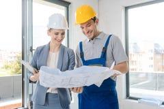 Trabalhador da construção e arquiteto que olham o plano no local fotos de stock royalty free