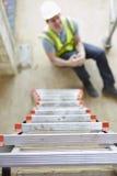 Trabalhador da construção Falling Off Ladder e pé do ferimento foto de stock