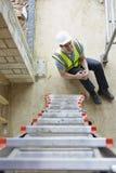 Trabalhador da construção Falling Off Ladder e pé do ferimento imagens de stock royalty free