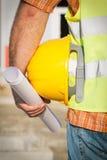Trabalhador da construção Holding Yellow Hardhat foto de stock royalty free