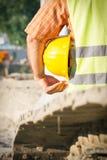 Trabalhador da construção Holding Yellow Hardhat fotografia de stock