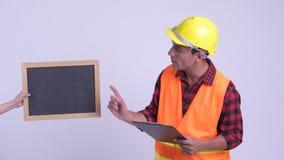 Trabalhador da construção latino-americano feliz novo do homem que apresenta com quadro-negro e prancheta