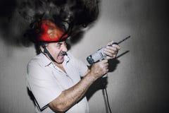 Trabalhador da construção masculino com uma broca e um shou cozinhando do capacete Fotografia de Stock