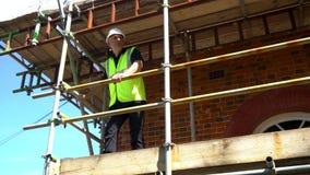 Trabalhador da construção masculino no terreno de construção com andaime e o céu azul vídeos de arquivo