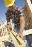 Trabalhador da construção Measuring Timber Foto de Stock Royalty Free