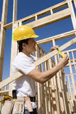 Trabalhador da construção Measuring Timber Fotografia de Stock