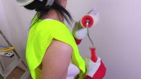 Trabalhador da construção da mulher que joga com rolo de pintura filme