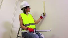 Trabalhador da construção da mulher que usa a fita métrica filme