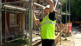 Trabalhador da construção no terreno de construção que inspeciona e que verifica o andaime filme