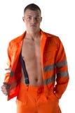Trabalhador da construção novo com o terno alaranjado aberto no torso despido Fotografia de Stock