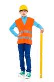 Trabalhador da construção pequeno que levanta com um nível de espírito Foto de Stock Royalty Free