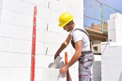 Trabalhador da construção da profissão - trabalho em uma construção do terreno de construção de uma casa residencial imagens de stock royalty free