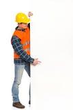 Trabalhador da construção que aponta na bandeira grande. Foto de Stock