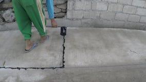 Trabalhador da construção que derrama o asfalto derretido quente entre blocos da junção de estrada video estoque