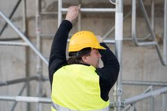 Trabalhador da construção que escala uma escada fotos de stock