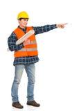 Trabalhador da construção que guarda o plano e apontar do papel rolado. foto de stock royalty free