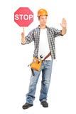 Trabalhador da construção que guarda um sinal da parada Foto de Stock Royalty Free