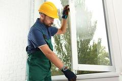 Trabalhador da construção que instala a nova janela imagens de stock