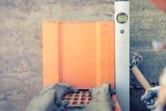 Trabalhador da construção que mede com os tijolos nivelados profissionais em paredes Imagens de Stock