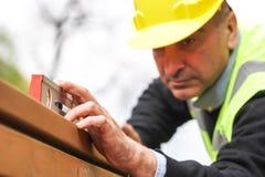 Trabalhador da construção que mede com um nível de espírito tubular imagens de stock royalty free