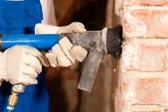 Trabalhador da construção que remove o emplastro fotografia de stock
