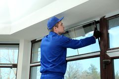 Trabalhador da construção que repara a janela fotos de stock royalty free
