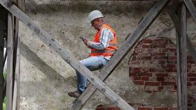Trabalhador da construção que senta-se no andaime de madeira e que usa o PC da tabuleta filme