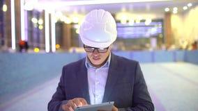 Trabalhador da construção que usa a tabuleta digital no local de trabalho arquiteto que usa a tabuleta video estoque