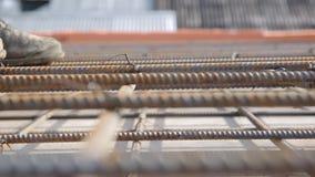 Trabalhador da construção uniforme velho na armadura amarrada no canteiro de obras, fim acima vídeos de arquivo