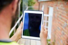 Trabalhador da construção Using Digital Tablet no terreno de construção imagem de stock