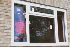 Trabalhador da construção Installing New Windows na casa Fotos de Stock Royalty Free