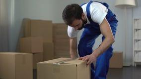 Trabalhador da empresa de mudanças com cuidado que embala e que leva caixas, serviços de qualidade filme