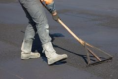 Trabalhador da estrada da construção que nivela o concreto fresco do asfalto Imagens de Stock