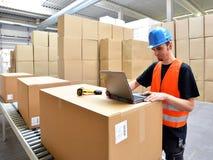 Trabalhador da logística - o homem faz a varredura de pacotes dos bens e prepara o d imagens de stock