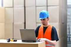 Trabalhador da logística - o homem faz a varredura de pacotes dos bens e prepara o d fotografia de stock