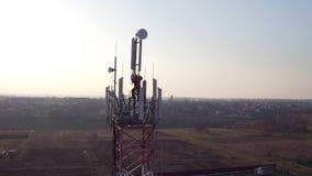 Trabalhador da manutenção que presta serviços de manutenção à antena celular na frente da luz solar, vista aérea da torre do tele filme