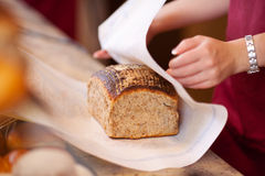 Trabalhador da padaria que envolve o pão no contador Imagens de Stock