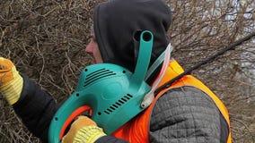 Trabalhador da paisagem com o cortador do arbusto perto do arbusto video estoque