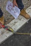 Trabalhador da pintura da estrada que guarda planos e que mede a fita Imagens de Stock
