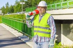 Trabalhador de construção de estradas com cone do tráfego foto de stock royalty free