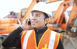 Trabalhador de construção de estradas na frente da máquina escavadora Fotografia de Stock